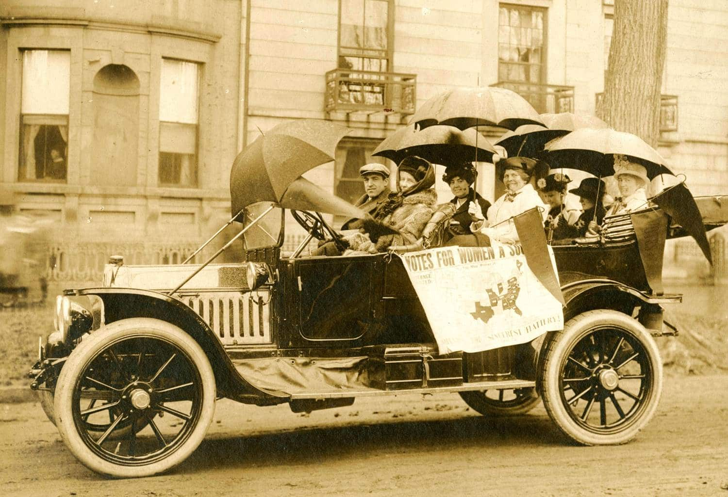 """Maine Suffragists in a Portland Maine parade, 1914. A group of people in a car on the street with umbrellas over their heads and a map of America that reads """"Votes for Women a Success."""""""