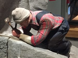 Mannequin wearing a hat, flannel shirt, and overalls. Bent over hammering into granite.