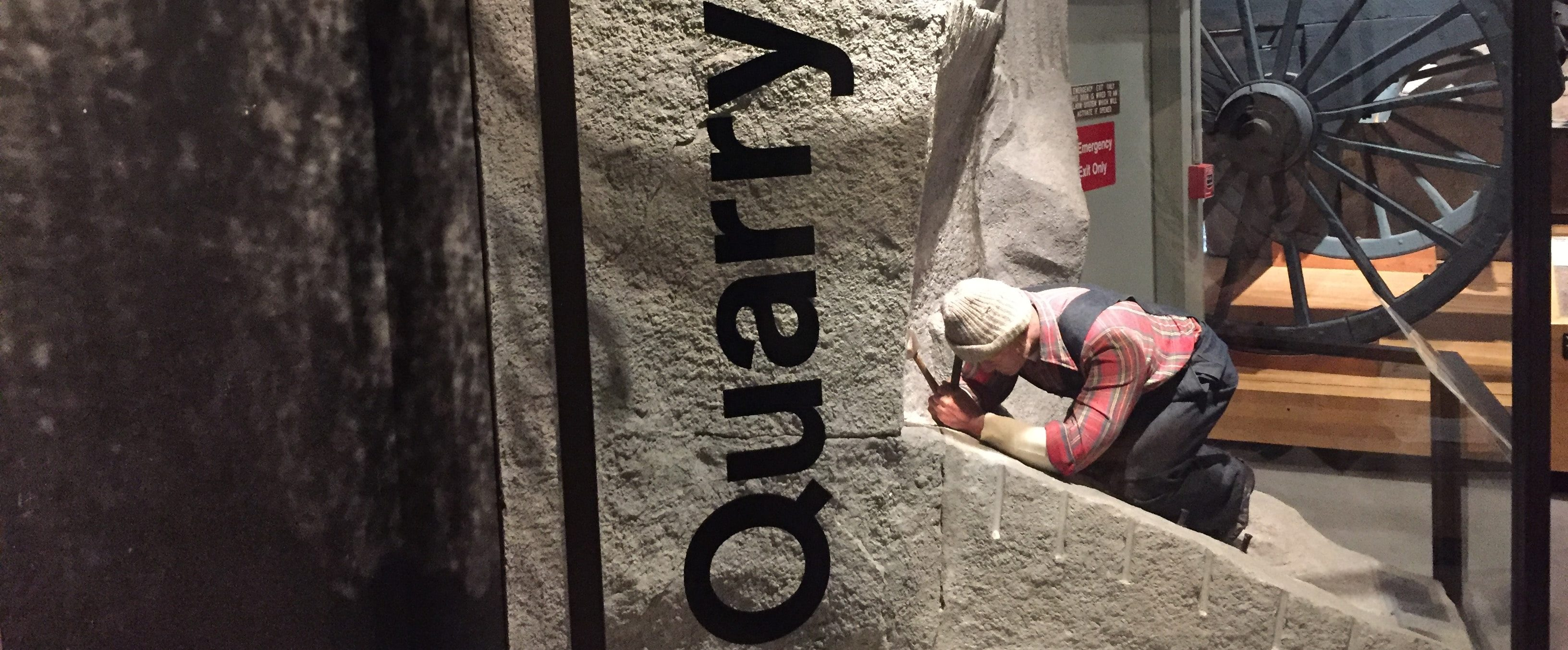 Granite exhibit in the museum, including a man working on a block of granite.